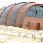 """""""Орбелус"""" Изба Orbelus, която носи древното име на Пирин – Орбел, и е първият български изцяло биосертифициран производител на вино, отскоро вече има и собствена изба. И то каква.Потънала сред лозовите масиви на петричкото село Кромидово, тя е с форма на... гигантска бъчва. Wow-ефектът е гарантиран още отдалеч. Проектът на архитектите Попова и Гочев е не само оригинален и интересен, но и в пълна хармония с тихия, топъл и успокояващ пейзаж, обграден от седем планини.Orbelus приемат и гости за дегустация и разходка в избата.Добрите новини са, че плановете включват изграждането на по-добър път към избата и хотелска част.За повече информация: www.orbelus.bg"""