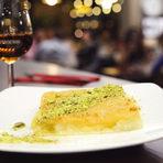 """За финала с десерта Тереза успокои """"Калории не броим в Ливан!"""", след богатата вечеря със завършек от ливанско кюнефе.Сладкишът с прясно сирене е обилно полят със захарен сироп, ароматизиран с розова вода и нероли – портокалови цветове.Ливан се яде основно на закуска, често в питка хляб. В София го опитахме с Hennessy Fine de Cognac и наистина забравихме да питаме за калориите, защото удоволствието не може да бъде спирано от броенето им. И накрая, за да бъде съвсем по ливански, нашата домакиня Тереза мина на сладка приказка с гостите за храната и приятната вечер, споделяйки им свои рецепти и кулинарни тайни. А ние си тръгнахме от гостуването сити и предоволни."""