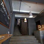 """Точно над Meat (на втори етаж) се забъркват едни от най-интересните коктейли в София. Bar Public e на година и половина. Пространството, в което се помещаваше аутлет се превърна в градско еклектично и в този смисъл уютно за бар. На терасата често се организират събития – този четвъртък например е посветен на дегустация на коктейли с нови словашки ликьори – Tratra Tea, които са цитрус, кокос и горски плодове на основата на чай.Съвсем новото лятно меню включва """"Маргарита"""" с тяхна лична интерпретация- текила, пюре от гуава, меден сироп и фреш от лайм. Съвсем авторски е Julep – уиски, пюре от капина, кокосов чаен ликьор. А за да се разбере, че наистина е лято негронито (джин и вермут) е на клечка и замразено като сладолед.Много добро впечатление прави, че Bar Public и Meat са се договорили и ако огладнеете, няма нужда да слизате до долу – те ви предлагат менюто с бургери, поръчват им по """"уоки-токито"""" и си получавате храната директно в бара. В петък и събота музиката се селектира от диджей и именно тогава работното им време е до 5:00 ч. сутринта, през седмицата обикновено заведението затваря в 2:00 ч., а всеки ден отваря в 17:00 ч.Bar Public, Ангел Кънчев 1"""