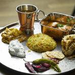 """Бътър мург масала е пилешко филе с лук, доматена салца, подправки и сметана. Кадай панир е традиционното индийско сирене с чушки, лук, грейви, куркума и сметана. В купичката беше поднесена лещата дал макхни, която, по думите на шеф Мишра, е любима на клиентите на ресторант """"Шафран"""". Приготвя се в продължение на 18 часа, а към нея се прибавя масло, сметана и мед. Към кулинарния разгул в платото с основното ястие се присъединиха и зеленчуково пулао - басмати със зеленчуци, бунди райта - салата от цедено мляко, печен кимион и пресен кориандър, и индийският хляб малабари парата.Изборът за бира беше точният: Hills Helles Rauch. Бирата допълваше ястието дори визуално - с интензивния си тъмно кехлибарен цвят и плътна пяна, с наситения си вкус и ясно изразен послевкус на пушено месо и дървесина."""
