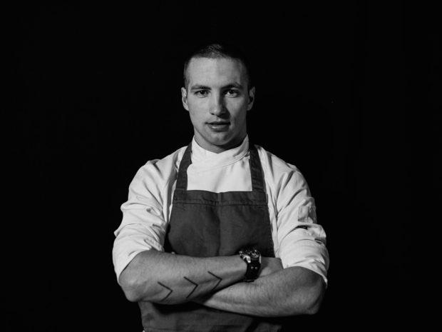 """Професионалната кариера на Валентин Иванов започва през 2011 година, когато завършва ТОХ в гр. Банкя и започва работа в хотел Хилтън. Там работи три години и половина под ръководството на готвачи като Жан Юбер Гарние, Габриеле Савини и Андре Токев. Следващата година и половина прекарва в Амстердам в ресторанта с две звезди Мишлен Librije Zusje с главен готвач Сидни Схуте, с след това - в Лондон в ресторанта на Хестън Блументал Dinner (No. 36 в света за 2016). В момента работи като Sous Chef в ресторант """"Космос"""".Професионалният му идол е бразилският топ шеф Алекс Атала, когото определя като рядко срещана комплексна личност, която поема социалната отговорност на това да бъде един от най-добрите в сферата, в която работи. Смята, че успехът на един рестoрант зависи от способността му да поддържа постоянно високо качество, а добрият готвач трябва да е постоянен и самокритичен. Посланието му към хората е да ценят вкуса в храната и да уважат продуктите.Валентин Ивнов ще приготви първото ястие от вечерята на Ресторант на годината - дехидрирано цвекло, сланина от Източно-балканска свиня, кисело зеле и манатарки. Вдъхновението за рецептата идва от посещението му в една къща за гости в село Горно Драглище, в полите на Рила планина. """"Посрещането, храната и цялото преживяване в една семпла и откровена обстановка те карат да се почувстваш все едно си се прибрал вкъщи"""", разказва той. """"С това ястие искам да покажа времето и мястото: къде се намираме и кое време на годината е. С локални продукти да поднеса ястие, което да припомни характерното за българите гостоприемство.""""Повече информация за менюто, събитието и как да закупите своя куверт може да намерите на сайта на Ресторант на годината или на фейсбук страницата на събитието./Снимка: Васил Германов/"""