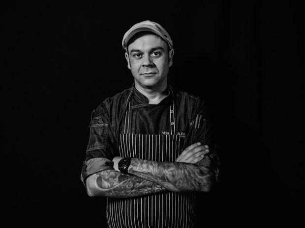 """Веселин Калев е работил в хотел """"Хилтън"""" под ръководството на Андре Токев, а през 2005 година е бил и част от екипа на Емил Минев в ресторант """"Талисман"""". Именно те го вдъхновяват да продължи по пътя на професионалното готварство. След това заминава в Германия, където за 10 години натрупва сериозен опит и работи в няколко ресторанта с една и две звезди Мишлен. През 2017 г. се завръща в България и става главен готвач на хотел """"Рила"""" в Боровец, където управлява три ресторанта и екип от 50 човека.Неговата супер сила са сосовете, а в ястията смята за най-важния компонент вкуса. Според Шеф Калев най-важното качество за успеха на един ресторант е постоянството, а най-непростимата грешка в кухнята - да си мислиш,че знаеш всичко. Добрият готвач по неговите думи е упорит и измерва успеха си с усмивките на клиентите. Посланието му към младите таланти е да не се предават.Шеф Калев ще приготви първото основно ястие по рецепта, разработена специално за Ресторант на годината - печен гълъб, карфиол, годжи бери, кедрови ядки и спанак. Идеята за ястието се е родила по време на разходка в планината, след като пада първият сняг. """" Кремът от карфиол символизира снежната покривка, а чипсът от зеленчуци са заснежените гори. Гълъбът е символа на свободата, която планината ни дава"""", споделя той.Повече информация за менюто, събитието и как да закупите своя куверт може да намерите на сайта на Ресторант на годината или на фейсбук страницата на събитието./Снимка: Васил Германов/"""