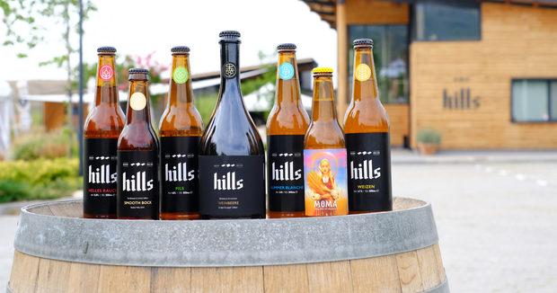 """Българската микро-пивоварна Hills Brewery, известна със спазването на """"Немския закон за чистота на бирата"""", отново ще ни гостува с 4 наливни и с всичките си 7 истински бири в бутилки. Наред с познатите ни рецепти, те ще ни представят и две нови серии, дело на българските майстори пивовари. МОМА Жътварка е най-новото им лятно изкушение – светло пиво 4.2%, обогатено с лимец и с три вида хмел от Велинград. А Хилс Вайнбеере е лимитарана серия лагер бира 6.5% –иновативна рецепта с ферментация на бял гроздов сок. Тоест крафт бира, каквато не сме вкусвали досега. РазБира се, закъде без класическите Пилз, Вайцен и Хелес Раух - с препечен малц, които ще се леят наливно от крана. И за капак, ще усвоим всички полезни вещества от бирите им, защото във всяка една бълбукат живи дрождени клетки. Какво повече? 😊"""