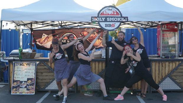 """The Holy Smokes BBQ е мобилна кухня вдъхновенa от американското барбекю и традиционната балканска скара. Обичат да смесват тези два различни свята и резултатът е уникално барбекю преживяване!Защо го правят?Защото обичат да правят хората щастливи и предават това щастие чрез езика на храната.Какво правят?Организират и участват в събития: в барове, ресторанти и градини като гост готвачи, частни партита и фестивали .С какво са различни?С вкусовете, които възникват благодарение на готвенето в затворени барбекюта и Тексаски опушвачи, така наречените Смоукъри .Ползват различни видове дървесина, която придава свои аромати на храната и характерните пушени вкусове.Самото преживяване:Дървото, металът и огънят са ключовите компоненти на техния стил. Тази визия ги отличава и едновременно ги прави автентични и стилни.Техните барбекюта, ''Holy Kitchen"""" бар кухня и екипът """"Holy Angels"""" създават специална атмосфера.С оригиналната декорация и презентация на храната, внасят специално и запомнящо се преживяване на всяко парти или събитие.С какво ще ни зарадват на феста:""""AK-47"""" (Пушени ребърца Трепач), """"Pull me under"""" (борд дърпано свинско месо), """"Holy Cow""""(борд дърпано телешко месо), """"Smoky Sausage""""(борд с пушени наденички), Snoopy Dog(хот дог с пушена наденичка), """"Knucklehead"""" (пушен свински джолан), """"Holy Grail""""(симбиоза от всички техни вкусове, всичко или нищо)."""