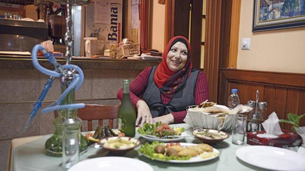 Фатима Хажи в ресторант Phoenicia. Пред нея: наргиле, Ksarak (ливанска ракия с вкус на анасон), кибе (продълговати топки от булгур с пълнеж), хумус, мутабал (от пасирани патладжани и тахан, поръсени със зърна от нар), постни сармички с домати и магданоз, табуле, и скара с пилешко и телешко месо.