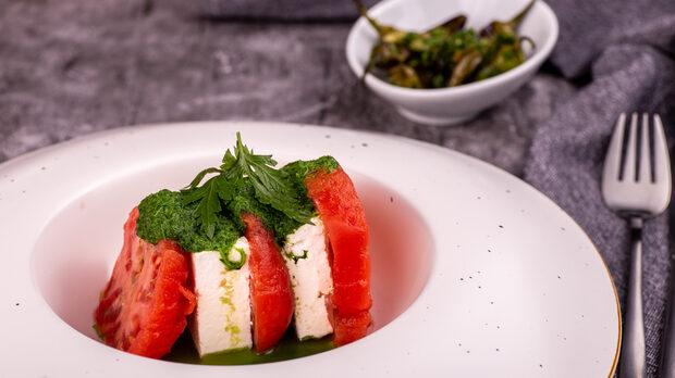 Предложение за сервиране на салата на емблематичния розов домат със сирене и модерен прочит на песто от магданоз