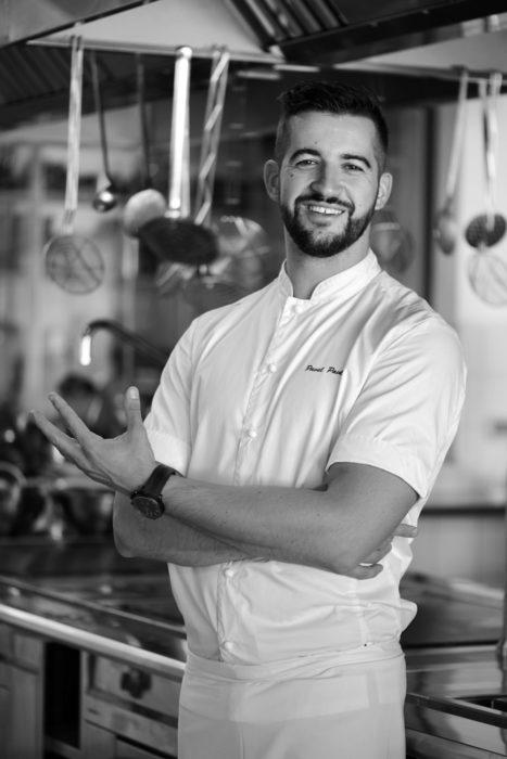 """Талантливият сладкар Павел Павлов е родом от Банкя и е възпитаник на HRC Culinary Academy. През 2010 г. заминава за Норвегия, където работи в ресторанта с една звезда Мишлен Renaa, както и в Bølgen og Moi и Tango. Там открива страстта си към сладкарството. Това го подтиква да отиде в Норвежкия институт по гастрономия и не след дълго става първият чужденец допуснат в националния отбор на Норвегия. През 2016 г. отборът печели два златни медала и се нарежда на четвърто място в света в Олимпийските кулинарни игри в Ерфурт, Германия. Към днешна дата Павел Павлов работи над мечтата си да развие собствена сладкарница в Норвегия.Избира тази професия, защото по думите му тя няма граници и всеки един ден предлага нещо ново и различно. Балансът между отделните компонентни и балансът на вкусовете е неговият измерител за добър резултат. Смята, че сред най-ценните качества на успешните хора в професията е желанието за развитие и способността да запази самообладание във важните моменти и да вземе правилното решение, а непроявеното уважение към клиента счита за непростима грешка. А на младите таланти би казал да не спират да изисквате от себе си и да не забравят, че всичко зависи само и единствено от тях.Павел Павлов ще приготви десертът за церемонията Ресторант на годината - """"Наполеон"""" от черен шоколад, матча чай, джинджифил и юзу цитрус. """"Обичам да се вдъхновявам от класически десерти и да ги презентирам пречупени през моя поглед и днешните тенденции в кулинарния свят. Затова избрах """"Милфьой"""" (на френски: Mille-feuille), в България и други страни е по-познат като """"Наполеон"""" - многопластов десерт"""", разказва ни той.""""В далечната 1651 година този десерт е създаден от французина Пиер Де Ла Варен. По време на вечерята ще ви представя една по-различна презентация с вкусове от Азия и един продукт любим на всички нас - шоколадът. Хрупкавата част от """"Наполеонът"""" е направена от черен шоколад и хрупкави палачинки, която гарнираме с тънки листа черен шоколад и кремю от матча, джинджифил и све"""
