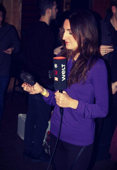 Репортерка от телевизионния канал Pro 7 разглежда с любопитство черен бейгъл в пряко включване от фестивала.Цялата статия може да прочетете тук.