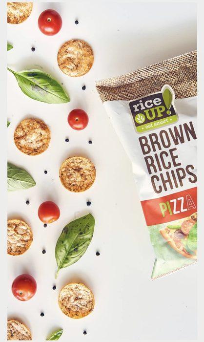 """RiceUP! е създаден, за да даде вкусна и полезна алтернатива за балансирано хранене – всеки ден, където и да сте. Техните продукти са направени от кафяв пълнозърнест ориз, защото е доказано едно от най-здравословните зърна. Той е богат на фибри, селен, витамини от група В и е без глутен. Всички техни продукти са само с натурални съставки, без мая и без пържене.Независимо дали изберете да опитате """"сандвич"""" от оризова бисквита, вкусна бисквитка с белгийски шоколад, оризов чипс или оризово ролце, можете да бъдете спокойни, че сте направили най-добрия избор. Пълнозърнестите оризови снаксове са истинско удоволствие за сетивата – хрупкави, с изтънчен или изразителен вкус и най-важното – 100% натурални.Затова на щанда на RiceUP! ще присъстват познатите ви вкусотии от пълнозърнест кафяв ориз, които ще имате възможност да опитате и закупите.Пригответе се и за специална изненада - те поканиха по време на базара Анелия Калчева, създател на кулинарния блог за вкусни и полезни изкушения – Healthylicious heaven. Ани ще демонстрира на посетителите ни набор от апетитни, здравословни и лесни за приготвяне рецепти с продуктите на RiceUP!, които – както сами ще се убедите, са приятен и здравословен заместител на традиционните снаксове, вредните чипсове и дори на хляба, който се нарежда сред едни от най-важните продукти в потребителската кошница на българина. Заедно, те ще ви разкрият тайни за приготвянето на вкусна, здравословна и балансирана храна, които можете да използвате в ежедневието си. Всичко за първия Бакхус Коледен Гурме Базар вижте тук.Научавайте новостите за събитието във Facebook.Купете билет онлайн с намаление тук."""